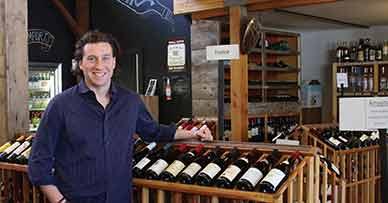 Gavin Fine smiling in front of wine rack